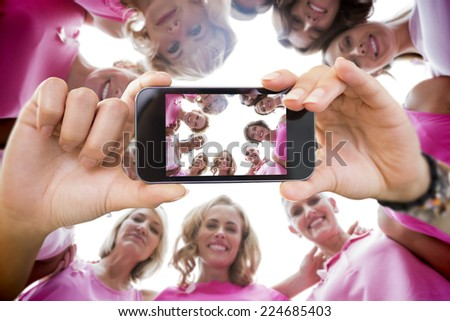 Composite image of hand holding smartphone showing photograph of breast cancer activists - stock photo