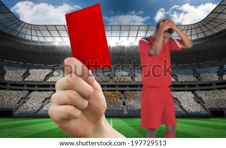 Composite image of hand holding up red card to player against stadium full of argentina football fans - stock photo