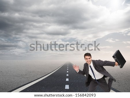 Composite image of happy businessman holding a briefcase and running over street under cloudy sky - stock photo