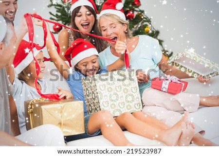 Composite image of Happy family at christmas opening gifts together against snow - stock photo