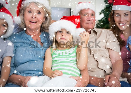 Composite image of Happy multigeneration family wearing santa hats on the couch against snow falling - stock photo