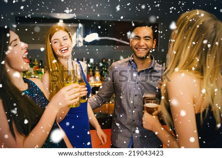 Composite image of Laughing friends drinking beers against snow falling - stock photo
