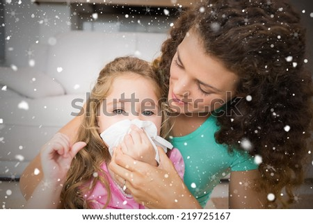 Composite image of mother helping her daughter blow her nose against snow falling - stock photo