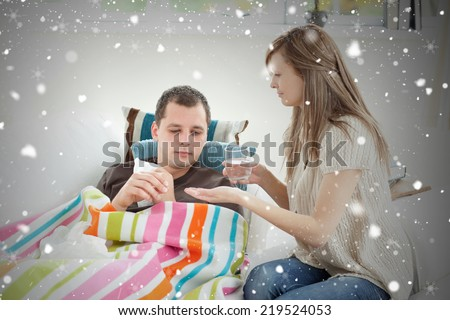 Composite image of positive woman taking care of her husband against snow falling - stock photo