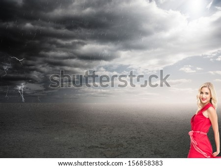 Composite image of pretty blonde in red dress posing and smiling under a stormy sky - stock photo