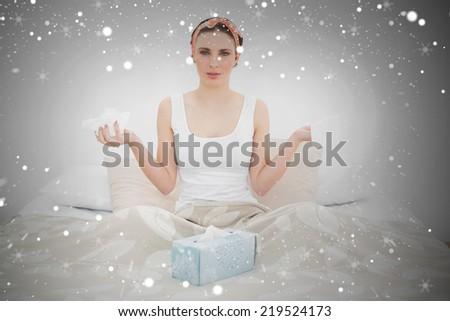 Composite image of sick woman holding handkerchiefs against snow - stock photo