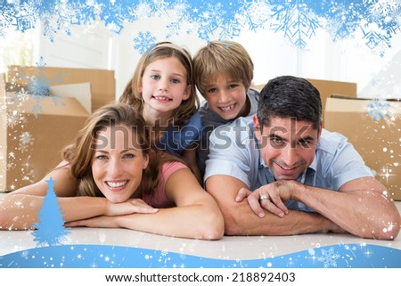 Composite image of snow frame against family lying on floor in new house - stock photo