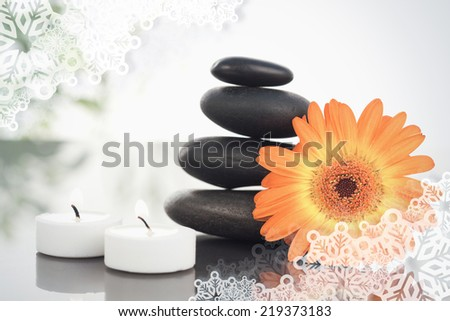 Composite image of snowflake frame against lighted candles pebble stack an orange gerbera - stock photo