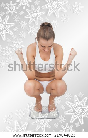 Composite image of Successful young woman crouching on a scales with snowflakes on silver - stock photo