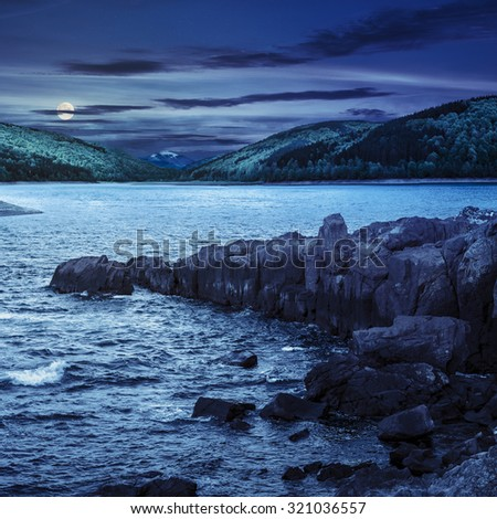 composite image of summer landscape  on lake with rocky shore and some boulders near forest in mountain  with high peak far away at night in full moon light - stock photo
