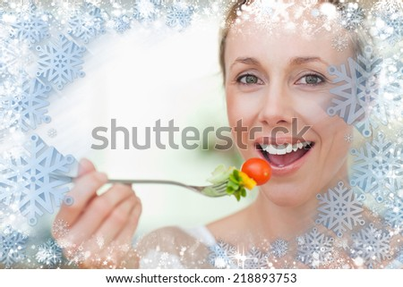 Composite image of woman having some salad against snow - stock photo