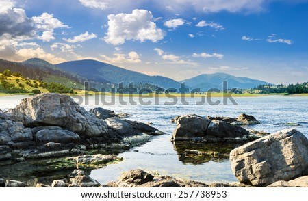 composite landscape with rocky lake shore and some boulders in mountains in morning light - stock photo