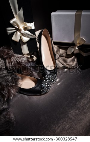 Composition black shoes with spikes and gift boxes, silk background - stock photo
