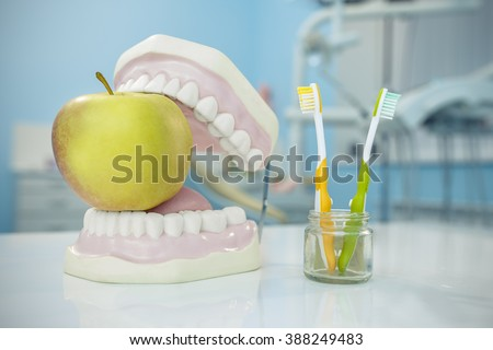 Composition. Denture, apple and toothbrushes in glass in dental surgery - stock photo