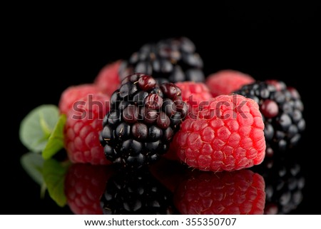Composition from a blackberry and raspberry on the black isolated background - stock photo