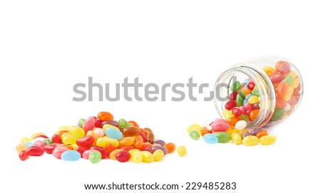Composition of a glass jar and multiple colorful jelly bean candies, isolated over the white background - stock photo