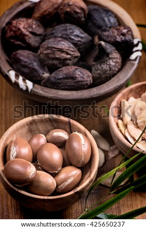 Composition of argan fruits, seeds and oil for skin care - stock photo