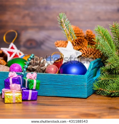 composition of branch fir tree, vintage wooden box with Christmas decoration, pinecones, stars, balls and gifts on wooden background, close up - stock photo