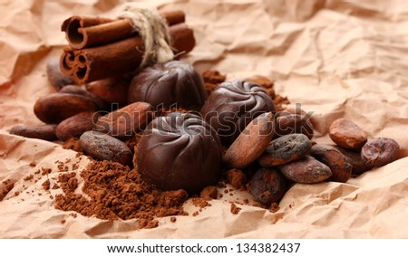 Composition of chocolate sweets, cocoa and  spices on brown background - stock photo