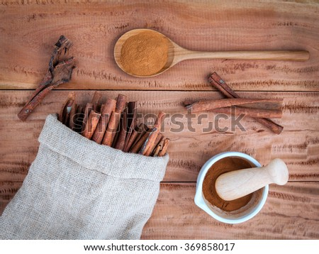 Composition of cinnamon stick in hemp sack and cinnamon powder in white mortar and  cinnamon powder in wooden spoon on rustic old wooden background . - stock photo