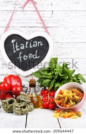 Composition of colorful pasta, fresh tomatoes, basil, olive oil in bottle on wooden background - stock photo