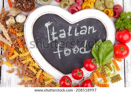 Composition of colorful pasta, fresh tomatoes,basil on wooden background - stock photo