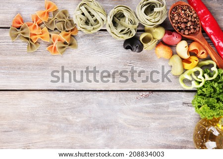 Composition of colorful pasta, fresh tomatoes, herbs on wooden background - stock photo