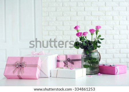 Composition of colourful gift boxes and flowers in glass on white table in front of brick wall background - stock photo