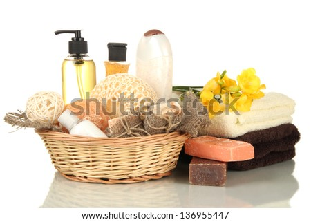Composition of cosmetic bottles and soap in basket, isolated on white - stock photo