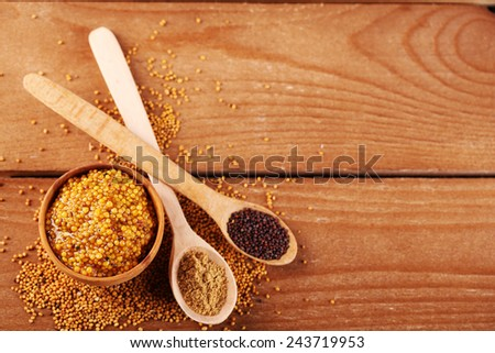 Composition of different kinds of mustard on wooden background - stock photo