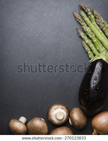 Composition of different organic vegetables, isolated on dark grey stone slab with copyspace. - stock photo
