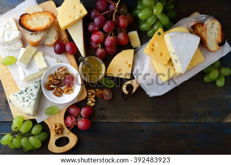 Composition of different types cheese on old wooden boards. Top view - stock photo