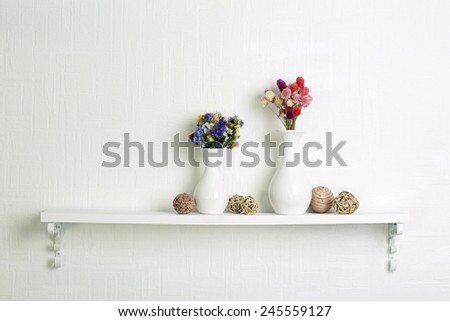 Composition of dried flowers on white wall background - stock photo