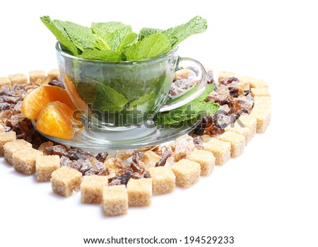 Composition of fresh mint leaves in glass cup and brown sugar isolated on white - stock photo