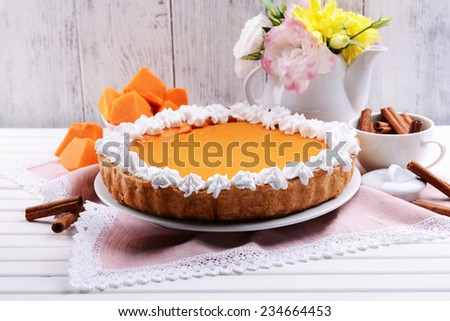 Composition of homemade pumpkin pie on plate and flowers in vase on wooden background - stock photo