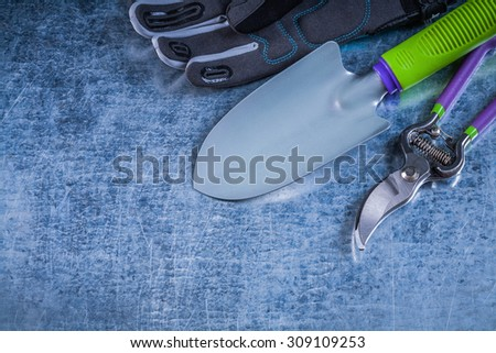 Composition of metal trowel secateurs protective gloves on metallic background. - stock photo