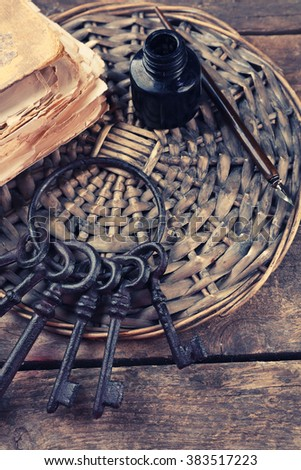 Composition of old books, keys and other things with wicker plate on wooden background, close up - stock photo