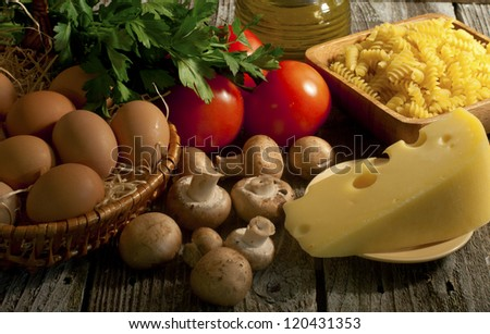 Composition of pasta, tomatoes, cheese, olive oil and mushrooms. - stock photo