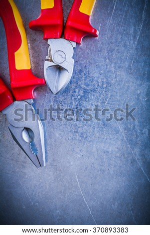Composition of pliers wire-cutter on metallic background electricity concept. - stock photo