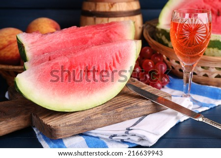 Composition of ripe watermelon, fruits, pink wine in glass and wooden barrel on color wooden background - stock photo
