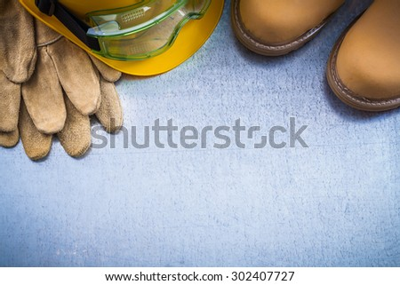 Composition of safety waterproof boots leather gloves building helmet and working glasses on scratched metallic background construction concept. - stock photo