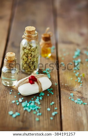Composition of soap bar bound by thread, sea salt and bottles with natural bath essences - stock photo