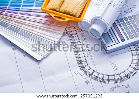 composition of tools stack rolled up white blueprints calculator paintbrushes in paint can - stock photo