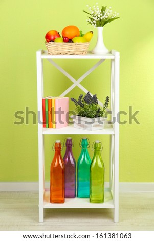 Composition of various home furnishing on white shelf on green wall background - stock photo