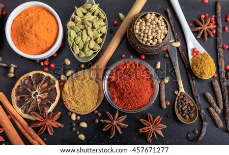 Composition of various spices on a black background - stock photo