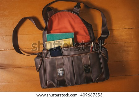 Composition of Vintage leather bag and old books on wood - stock photo