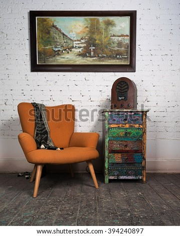 Composition of vintage orange armchair, colorful cupboard, aged wooden radio and hanged painting - stock photo