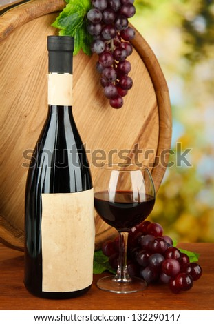 Composition of wine, wooden barrel and  grape, on bright background - stock photo