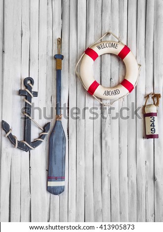 Composition on the marine theme with anchor, paddle and lifeline on old wooden background - stock photo