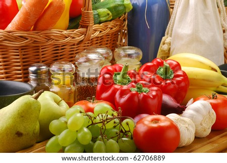 Composition with basket and vegetables on kitchen table - stock photo